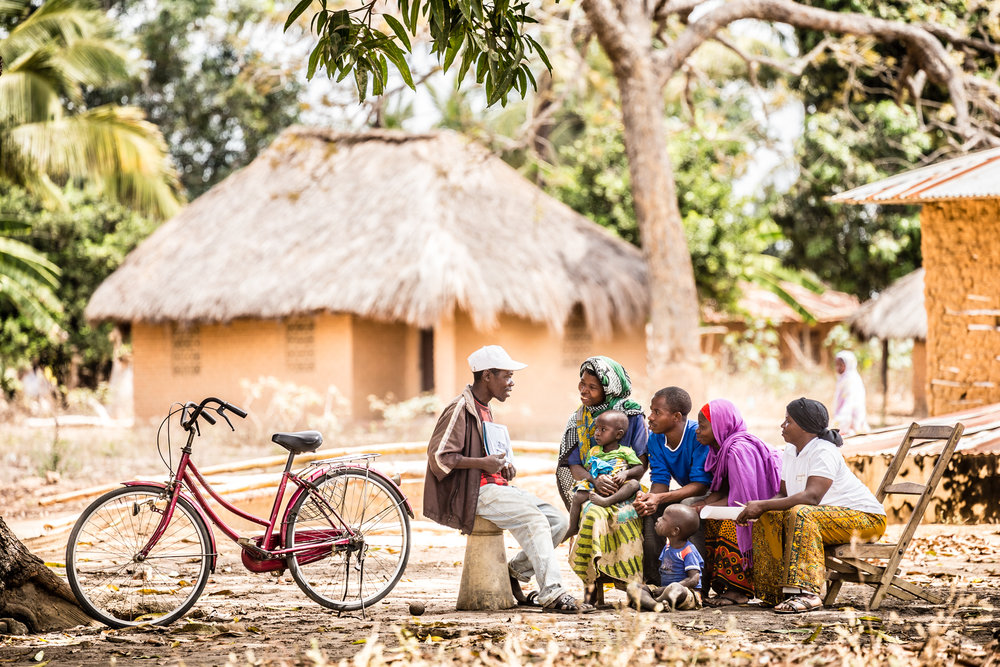 Community health worker discussing malaria and maternal health care with a family in Mikuyu village.