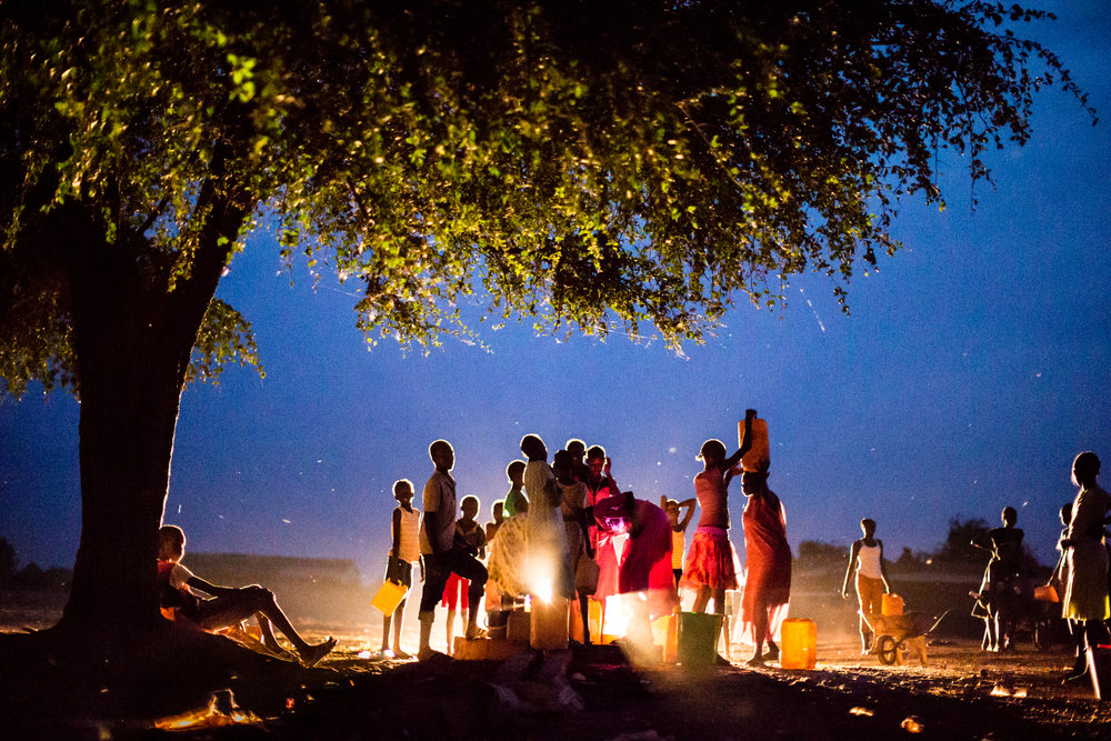 Children collect water at dusk in Kuajok. With few functioning boreholes in Warrap, pressure on the ones that work can be intense. When disagreements occur, they can escalate quickly and violence is not uncommon as families and communities step in to defend their side. Warrap State, South Sudan.  From Saferworld's 25th anniversary exhibition   Communities first  , funded by the Kingdom of the Netherlands.