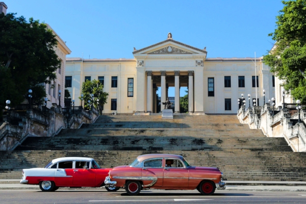 Classic American cars ride past the historic steps of La Universidad de la Habana