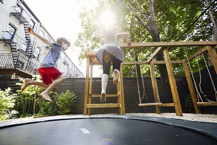 An in-ground trampoline plus a custom play structure which allows for swings, climbing, pretend play, and a ladder to get to the green roof above the cabin creates a beautiful adventure space for the children.     Photo by Shannon Greer.
