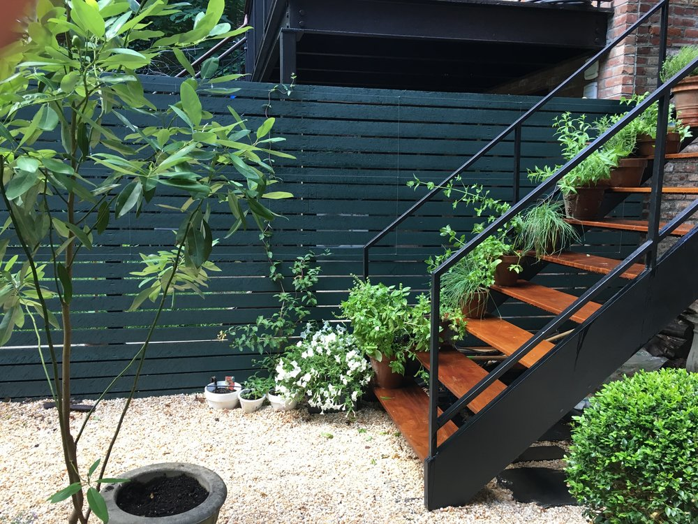 Simple terracotta herb planters on the ipe steps.