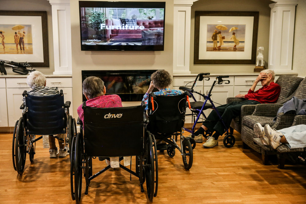 "A group of patients watch television in the common room at the Rosewood Village assisted living home on Greenbrier Drive after lunch. The floor is dedicated to the patients suffering from dementia, many of which are under the hospice care of Lee Read, a case worker with Hospice of the Piedmont. From the story ""Dying with Dignity"" in Charlottesville, Virginia."
