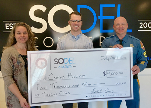 Check presentation attendees shown are (l-r) Lindsey Barry, SoDel Cares president and SoDel Concepts controller; Brenton Lyman, general manager of Matt's Fish Camp in Bethany Beach; and Master Cpl. James Hatfield of Camp Barnes. SUBMITTED PHOTO