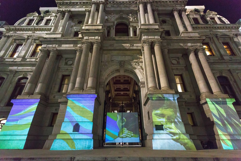 Seguimos Caminando (We Keep Walking)   Michelle Angela Ortiz  Born in 1978 • American/Latina • Based in Philadelphia Animation and projection City Hall   Photo courtesy of the artist.