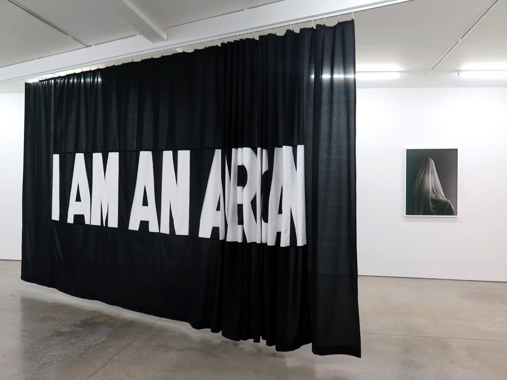"""I AM AN..."" 2017, sewn cotton panel on moveable ceiling track, 9' x 24' and ""Total Transparency Filter (Portrait of N),"" archival pigment print, 30"" x 40"" (Courtesy of the Artist.)"