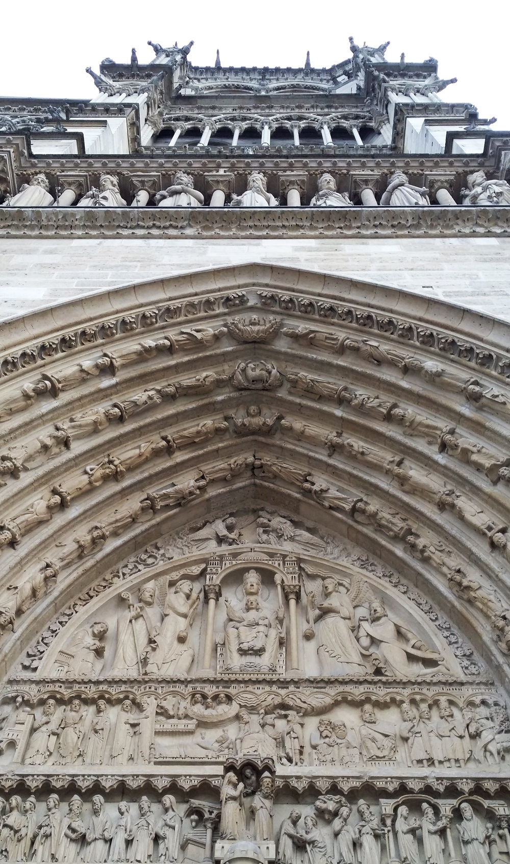 the carvings at the doorway of the entrance into Le Notre Dame Cathedral.