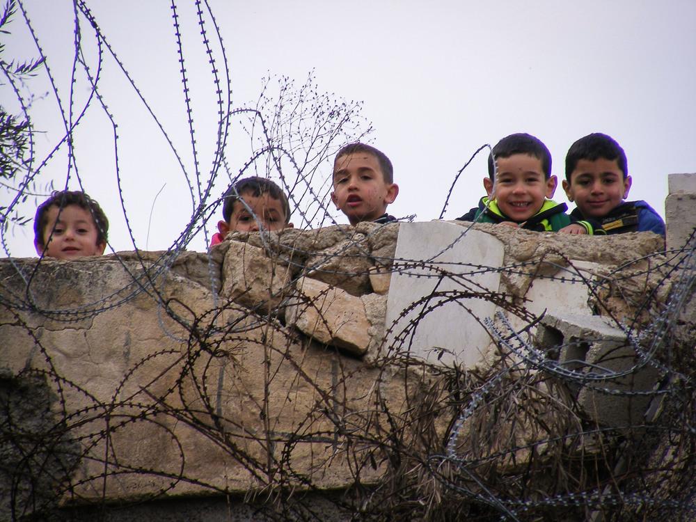 Kindergarten children smile and greet us, despite the razor wire they look through.