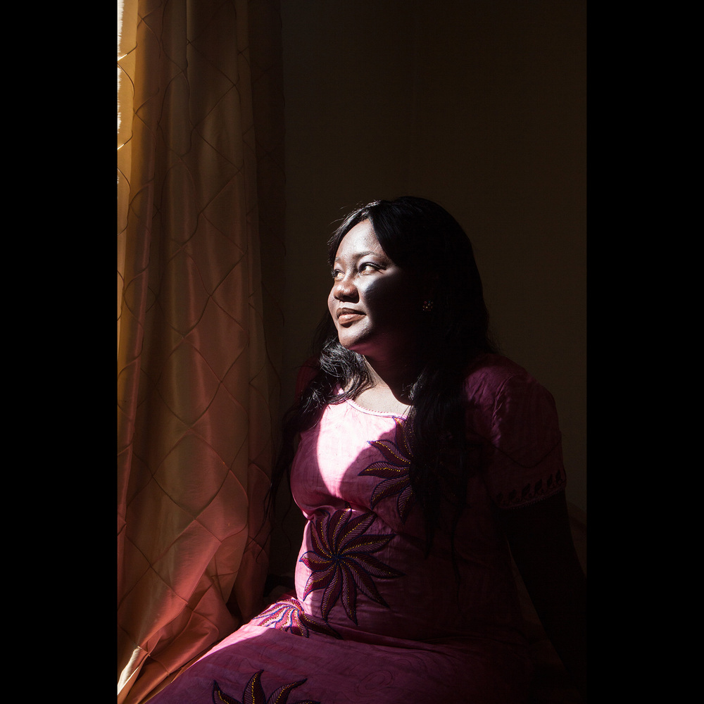 "Micheline is from Burkina Faso in West Africa. She speaks French and Moré. In December 2014, with a valid U.S. visa in hand, she came by plane to New York, where she was immediately apprehended by customs after declaring asylum, and was coerced into signing documents in English, without a translator. Telling her they would bring her ""someplace safe,"" she was transported to the Delaney Hall detention center in Newark, NJ. The facility faces the Essex County prison and is adjacent to the Newark power plant. For the next 7 months, depressed and scared, she waited until she was granted asylum and released in May 2015. In that period she had minimal phone contact with family and did not go outside. University educated, with a stable job at a multi-national company, she saw a bleak future amid growing terrorism and political unrest in her country, but her main reason for leaving was to escape an abusive marriage."