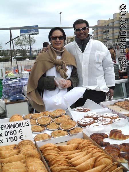 santa pola market pastry vendors: spain santa Pola Saturday market, pastry, empanadilla, ensaimada, filled sweet buns, thin pastry filled with membrillo (quince)