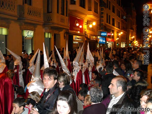 spain elche, Brotherhood long pointed white hood, long capes, procession, near Townhall, crowded street parade