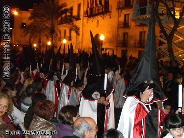 spain elche, Brotherhood long pointed hat hood, long capes carry candles, procession, at Elche Ayuntamiento, Townhall, crowded street parade