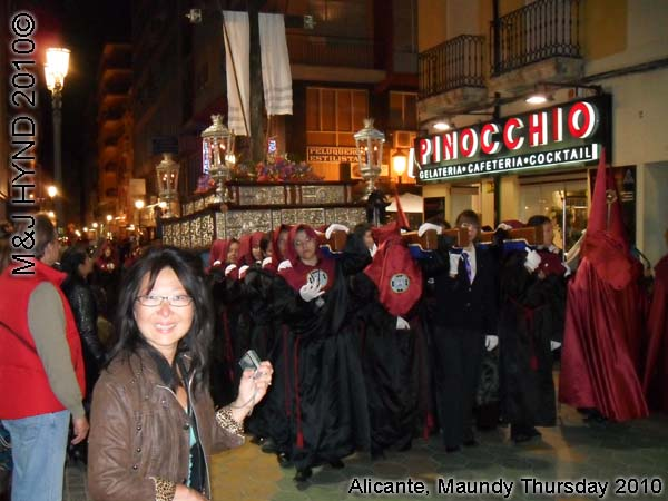 spain Alicante, Semana Santa Holy Week, Maundy Thursday procession, Brotherhood long pointed red hood, long capes, paso-bearers religious floats, silver Jesus's sculpture, somber march
