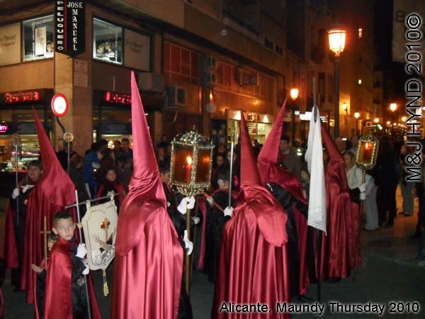 spain Alicante, Semana Santa Holy Week, Maundy Thursday procession, Brotherhood long pointed red hood, long capes carry lamps on poles, flag-bearers, somber march