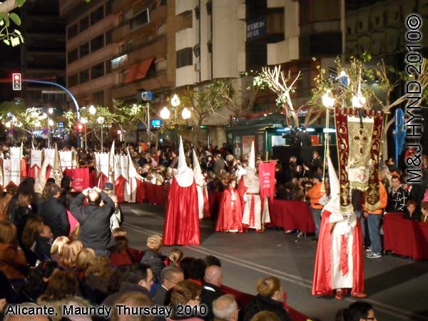 pain Alicante, Semana Santa Holy Week, Maundy Thursday city procession, Brotherhood long pointed white hoods, long capes carry lamps on poles, flag-bearers, marching bands
