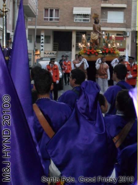 spain Santa Pola, Semana Santa Holy Week, Good Friday procession, Brotherhood long capes, paso-bearers religious floats, Jesus's sculpture, somber march, long pointed blue hood, uniforms