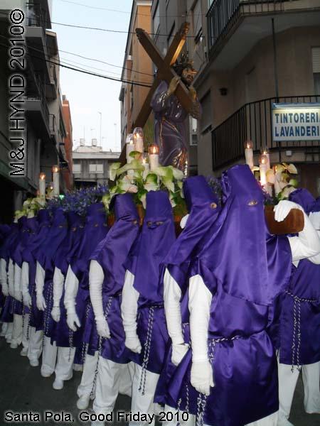 spain Santa Pola, Semana Santa Holy Week, Good Friday procession, Brotherhood long capes, gloves, paso-bearers religious floats, Jesus's sculpture, somber march, blue hood, uniforms