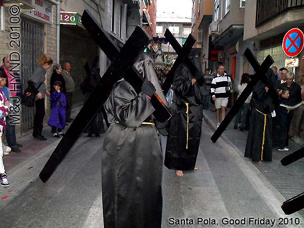spain Santa Pola, Semana Santa Holy Week, Good Friday procession, Brotherhood hooded, long black capes Penitents, bare-footed, carry huge black cross, somber march, long pointed blue hood, uniforms