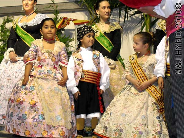on stage 3 littlies, 2 teenagers: spain perleta maitino St Vicente de Ferrer Fiesta, kings queens ladies-in-waiting, traditional long ballgowns, boys tuxedo, winner's sashes, stage