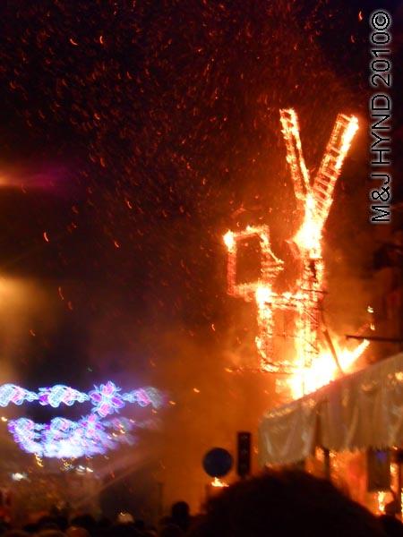 burning hoguers looks like windmill: spain Alicante Fiesta Hogueras de San Juan Bonfires of Saint John, firehoses douse burning, up in flames, International Tourist Interest, celebrate summer solstice