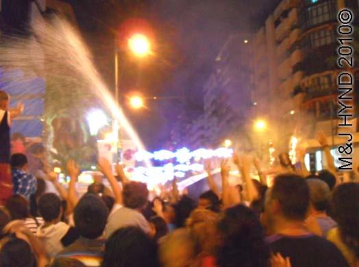 crowd with water / firehose: spain Alicante Fiesta Hogueras de San Juan Bonfires of Saint John, firehoses douse burning, crowds chant pick-me to firemen, International Tourist Interest, celebrate summer solstice