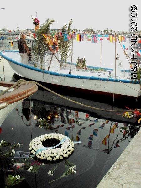 wreath in the water: spain santa Pola Fiesta La Virgen del Carmen, patroness of fishermen, fishing boats, flags buntings, wreaths