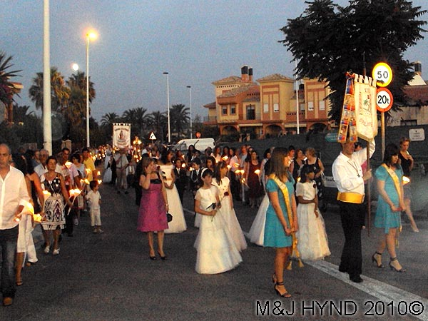 sombre parade: spain valverde fiesta  La Virgen de Santa Ana, candle-lit procession, traditional baptism dressed in white, flag-bearers
