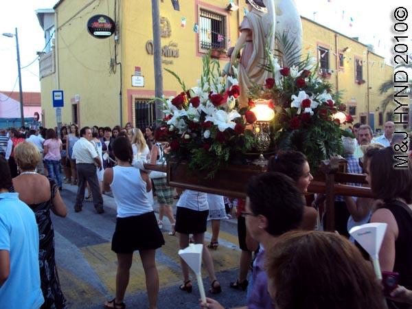 paseo / saint on the plinth:; spain valverde fiesta  La Virgen de Santa Ana, flags buntings, candle-lit procession, paso-bearers, religious floats, image sculpture of Santa Ana