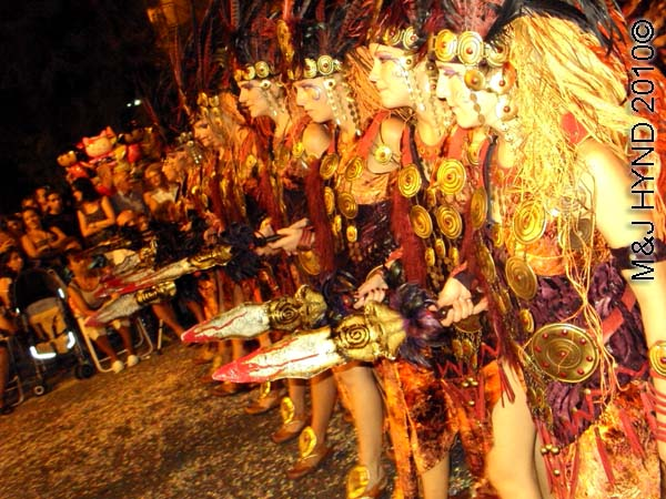 parade – red+gold: spain Santa Pola Annual Fiesta, procession Moorish warrior women, carry mock spears, confetti