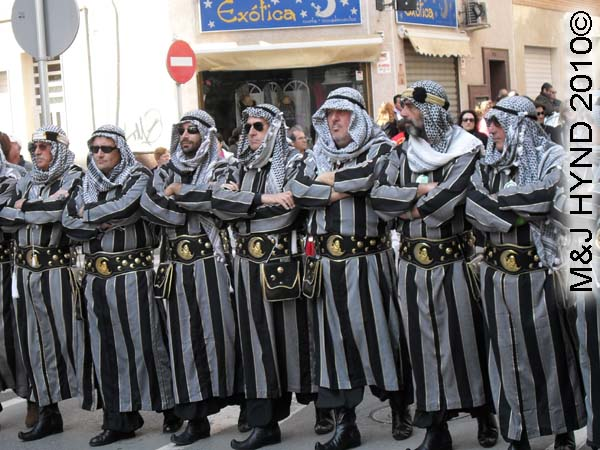grey+black striped: spain Santa Pola Annual Fiesta, Moorish men, costumed grey+black striped arm-in-arm procession