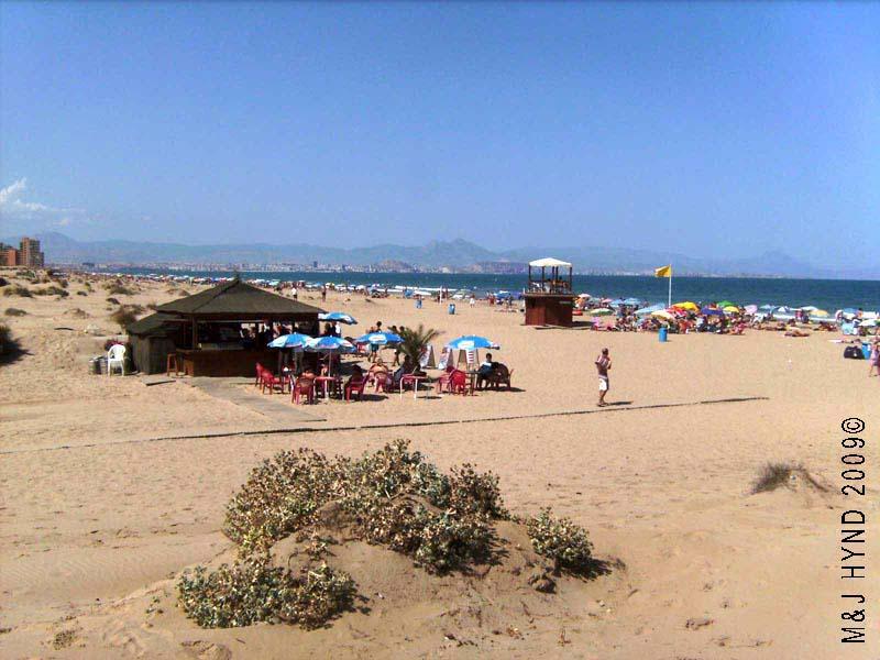 Spain Carabassi dunes golden sand beach Alicante city is nearby across Mediterranean sea; seasonal chiringuito, beachbar, in the foreground, sun umbrellas sunbathing