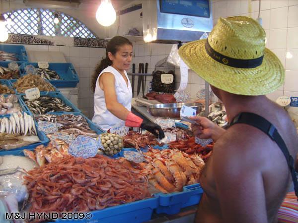 Spain Santa Pola fish market, prawns, squid, cigalas, tuna, clams, serving customers