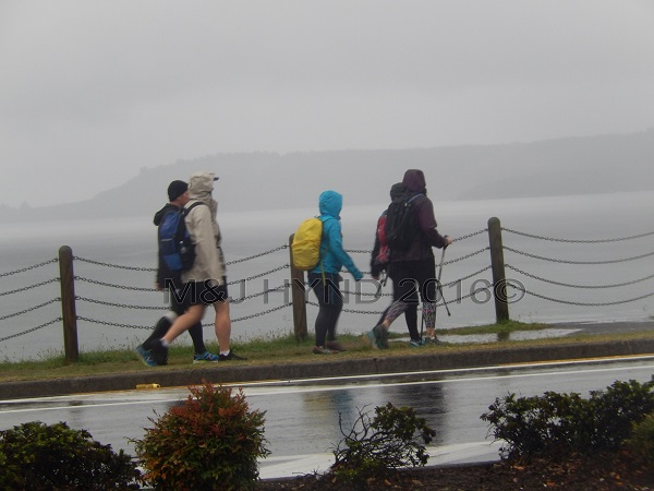 walkers in the rain at Lake Taupo edge, Taupo, NZ