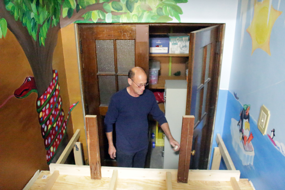 "Jim Horsham, 32° demonstrates the ""trap door"" which reveals the stairs to the Eastern Star supply room. When not in use, the area serves as a quiet play or reading nook for RiteCare children in Hastings."
