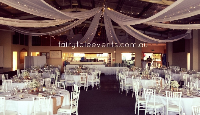 White silk drapes, fairy lights, linen & centrepieces by Fairytale Events.
