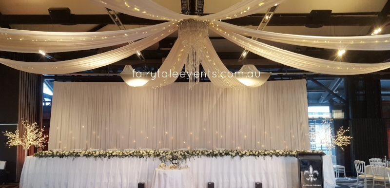 White silk drapes, fairy lights, chandelier LED trees by Fairytale Events