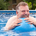 Man floating on ball in pool