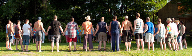 Men holding hands in circle outdoors