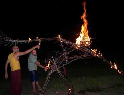 Two men setting fire to the sculpture