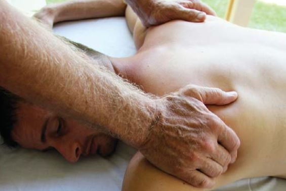 Laying man receiving massage on back