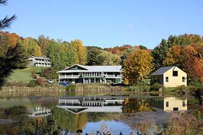 Guest House and Temple above the pond, with fall foliage in the background.