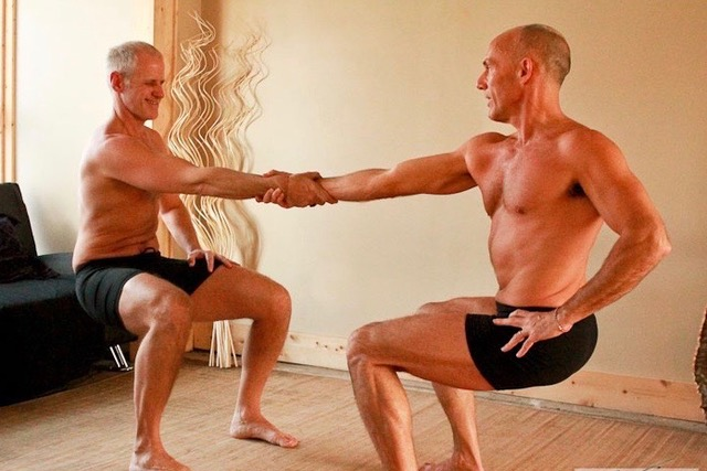 Two shirtless men squatting, facing each other, holding hands.