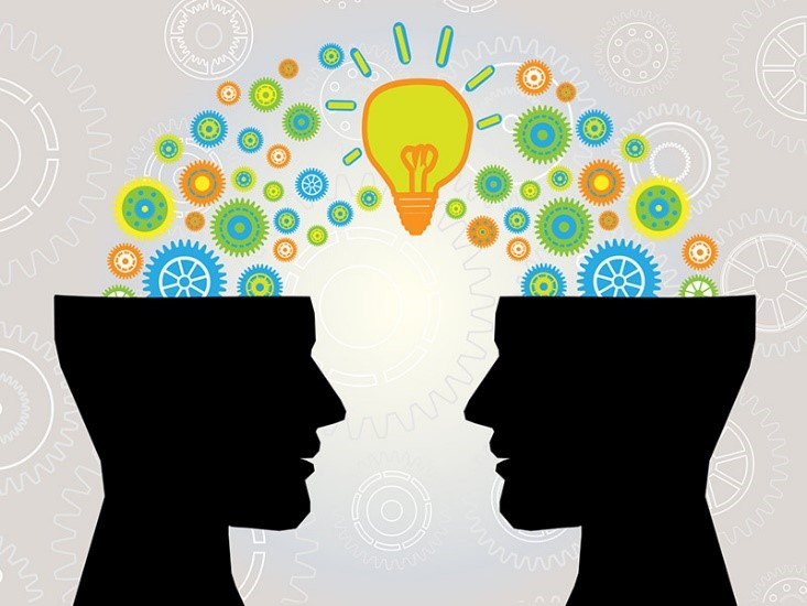 Two silhouettes of heads facing each other, topless, with the image of ideas going between the heads.