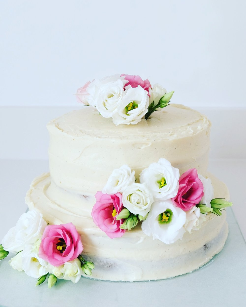 semi-naked carrot cake decorated with fresh flowers
