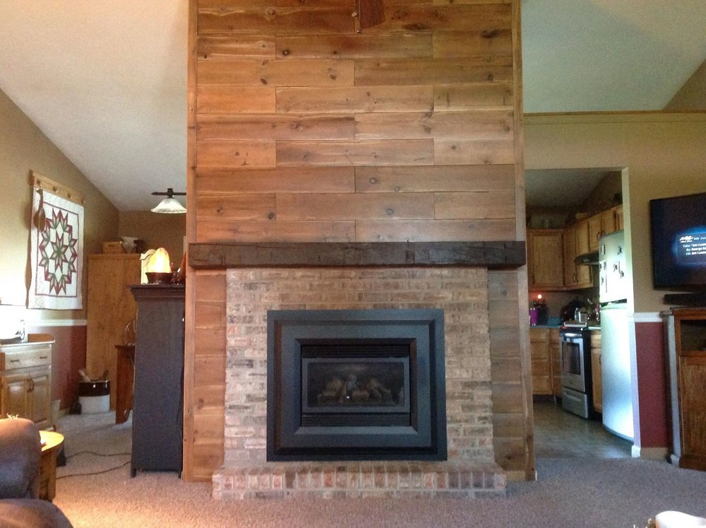 Reclaimed Barn Siding turned over o the brown side is the accent with a 5 x 10 inch Hand Hewn Mantle stained walnut.