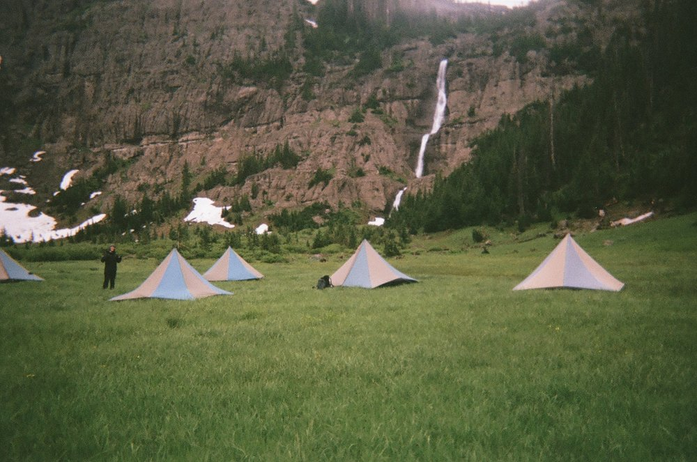 A rainy campsite below an icy waterfall.