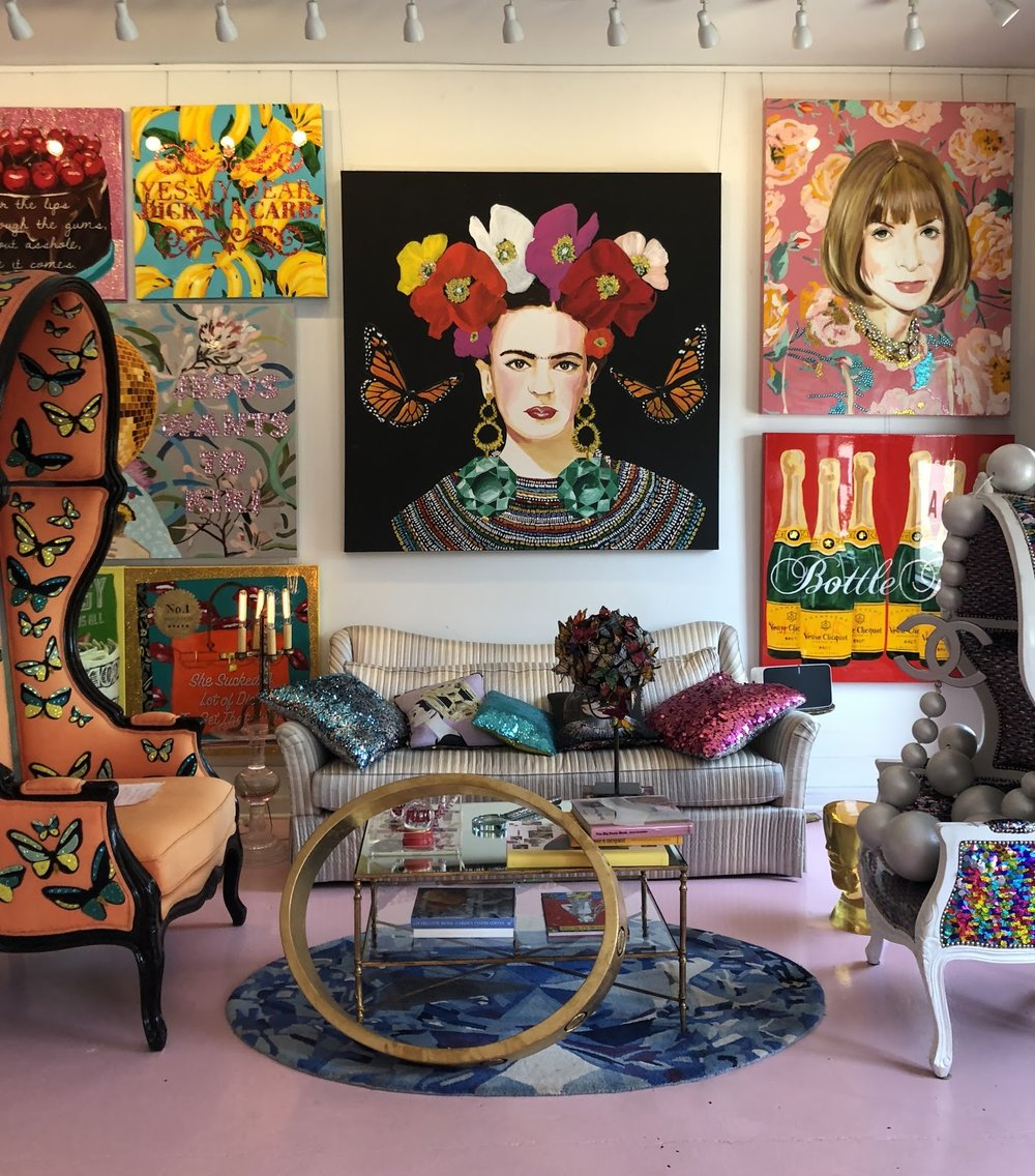 A sitting area in the studio with Frida Kahlo and Anna Wintour featured on the walls .