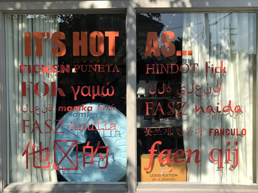 "The side window of the studio, with the words ""IT'S HOT AS F*CK"" in different languages ."