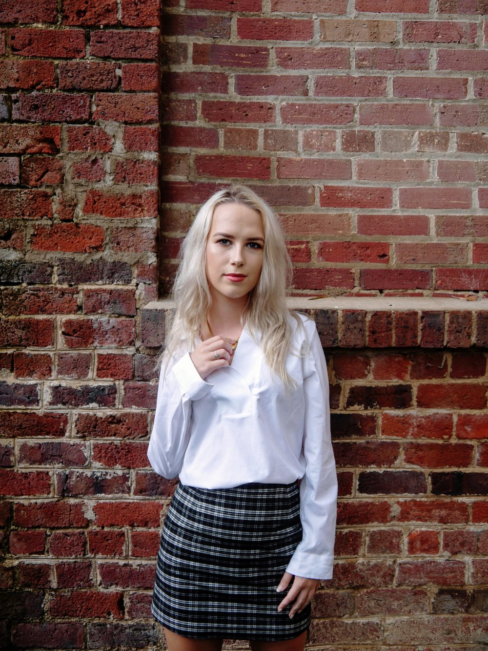 Anna, sophomore, wears a white TALBOTS shirt with a plaid mini-skirt from H&M.