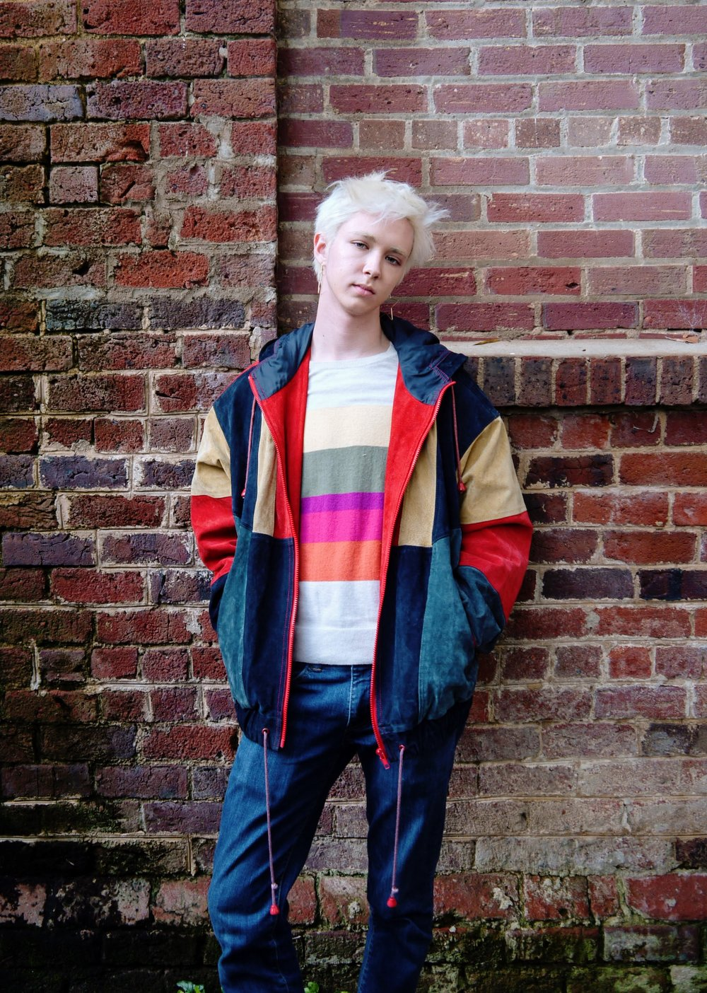 Indigo, freshman, wears a thrifted striped sweater underneath a colorful suede jacket, also thrifted. His earrings are from RUMORS.