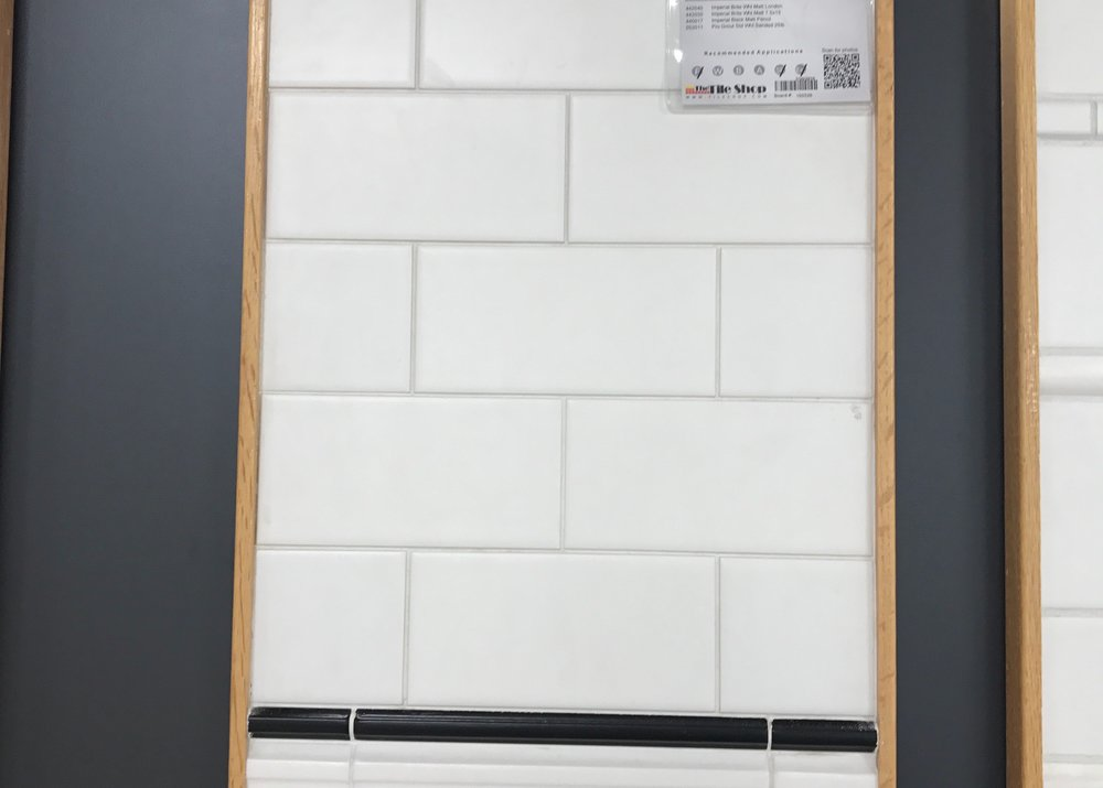 Matte Finished White Subway Tile With Black Trim.